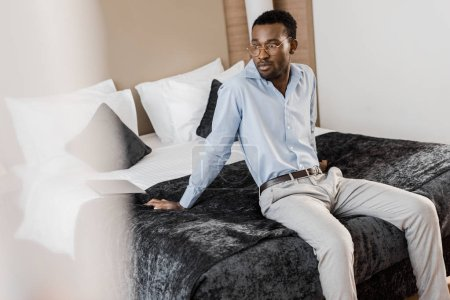 handsome african american man sitting on bed in hotel room