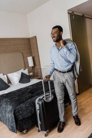Photo pour Heureux homme d'affaires américain avec sac de voyage en chambre d'hôtel - image libre de droit