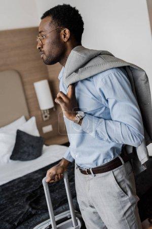 vue de côté d'homme d'affaires américain avec des bagages dans la chambre d'hôtel