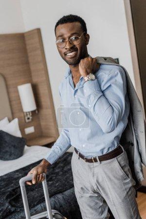 sourire d'homme d'affaires africain-américain avec la veste grise et sac de voyage en chambre d'hôtel