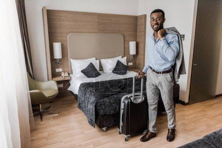 sourire d'homme d'affaires africain-américain avec la valise dans la chambre d'hôtel avec lit