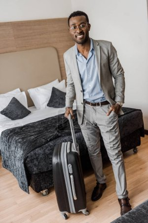 Photo for African american businessman in suit with suitcase in hotel room with bed - Royalty Free Image