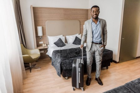 Photo for Elegant african american businessman with suitcase in hotel room with bed - Royalty Free Image