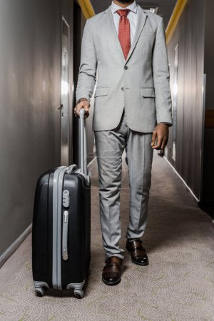 cropped view of businessman with baggage walking in hotel corridor