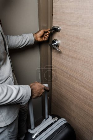 Photo for Cropped view of businessman with suitcase opening door with electronic key in hotel - Royalty Free Image