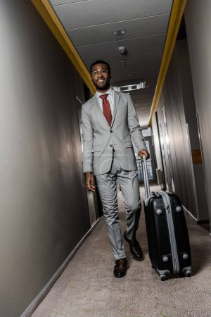 smiling african american businessman in suit walking with travel bag in hotel corridor