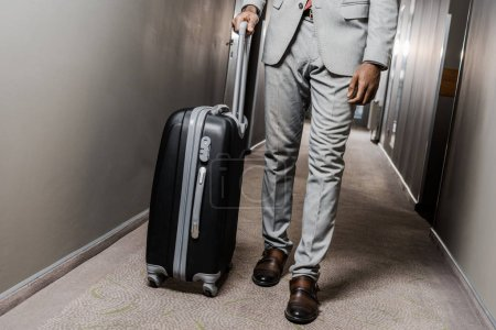 cropped view of businessman in grey suit with suitcase walking in hotel corridor