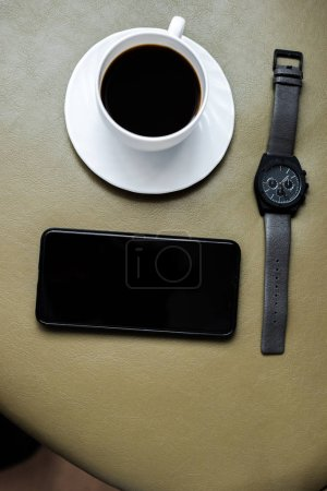 top view of coffee cup, wristwatch and smartphone with blank screen