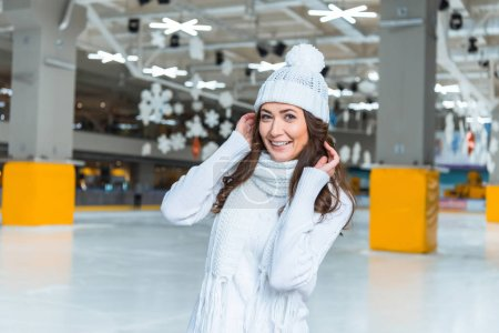 Photo for Portrait of smiling beautiful woman in hat and sweater looking at camera on skating rink - Royalty Free Image