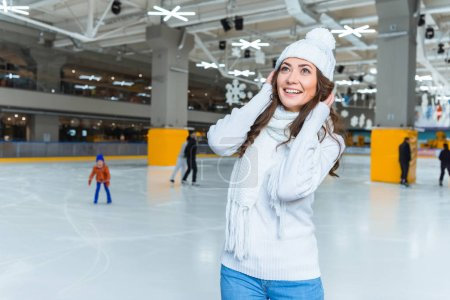 Photo for Portrait of smiling woman in knitted hat and sweater looking away on skating rink - Royalty Free Image