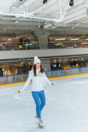 smiling young attractive woman in knitted sweater skating on ice rink alone