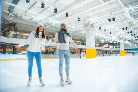 happy couple holding hands while skating on rink together