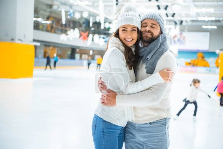 side view of couple in love hugging while skating on ice rink together