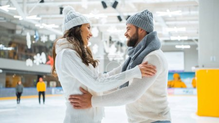 side view of smiling romantic couple on skating rink