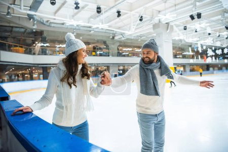 smiling couple in hats and sweaters holding hands while skating on ice rink