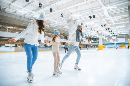 Photo for Smiling family holding hands while skating together on ice rink - Royalty Free Image