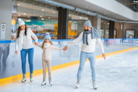 cheerful family in sweaters holding hands while skating together on ice rink