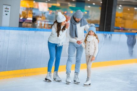 Photo for Smiling parents looking at daughter while skating on rink together - Royalty Free Image