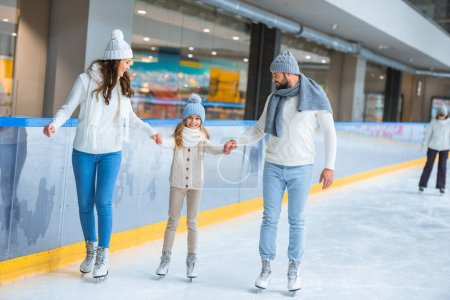 famiyl holding hands while skating on rink together