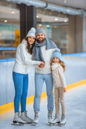 happy parents and daughter in sweaters looking at camera on skating rink