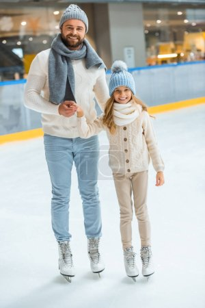 cheerful father and daughter holding hands while standing on skating rink