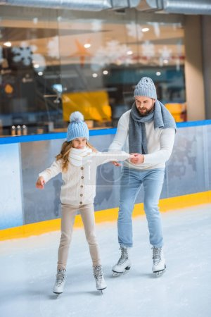 father helping little daughter to skate on ice rink