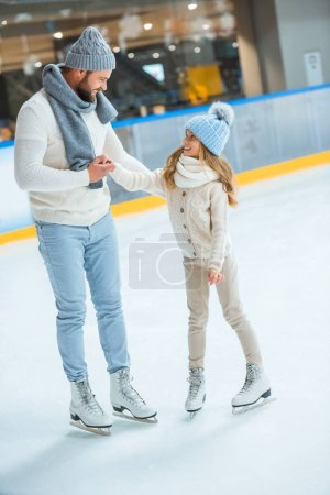 smiling father and daughter looking at each other on skating rink