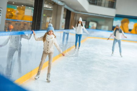 selective focus of kid skating on ice rink with parents behind