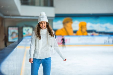portrait of smiling attractive woman in knitted sweater skating on ice rink alone