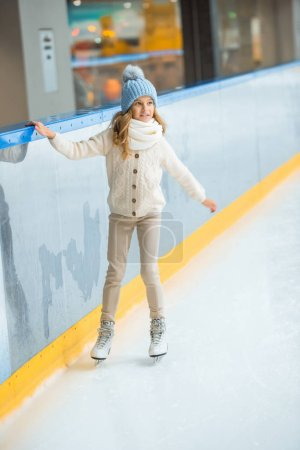 Photo for Little child in knitted hat and sweater skating on ice rink - Royalty Free Image
