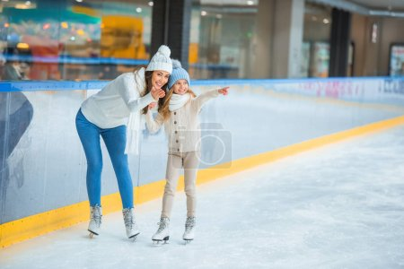 smiling mother and daughter pointing away on skating rink