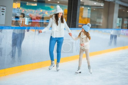 smiling mother and daughter holding hands and skating on ice rink together