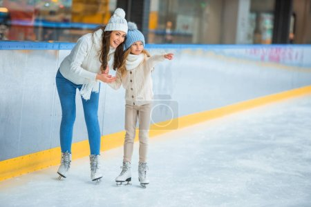 Photo for Smiling daughter showing something to mother on skating rink - Royalty Free Image