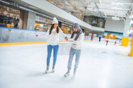 man teaching girlfriend how to skate on ice rink