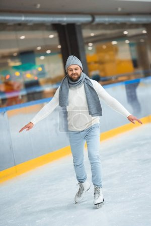 Photo for Bearded man in knitted hat and sweater skating on ice rink - Royalty Free Image