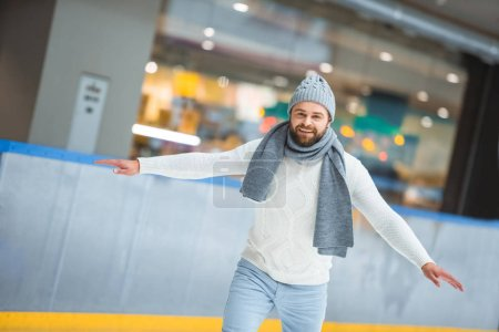 portrait of bearded man in knitted hat and sweater skating on ice rink