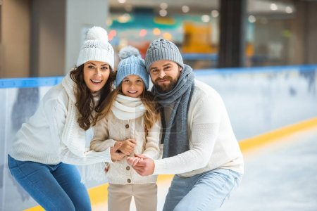 portrait of smiling parents and daughter in sweaters looking at camera on skating rink