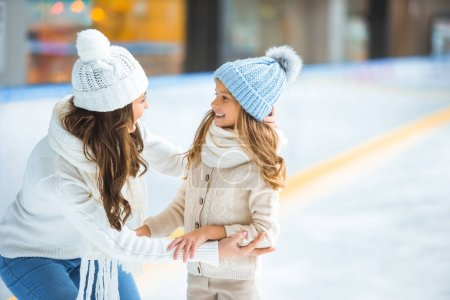 side view of happy mother and daughter looking at each other on skating rink