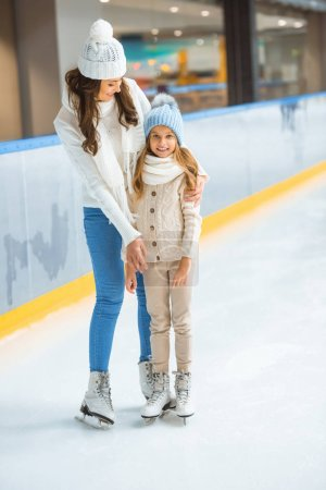 smiling kid and mother on skating rink