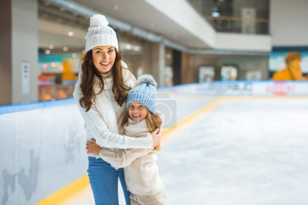 Photo for Portrait of mother and daughter hugging each other while skating on ice rink together - Royalty Free Image