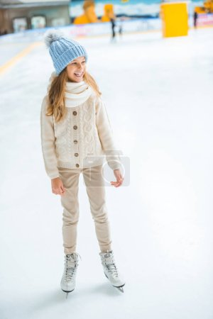 cheerful kid in sweater and skates looking away on skating rink