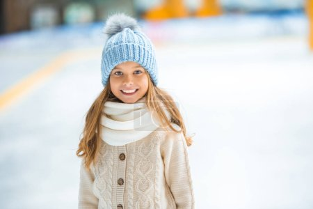 portrait of happy kid in knitted hat looking at camera on skating rink