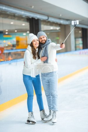 cheerful couple taking selfie on smartphone together while spending time on skating rink