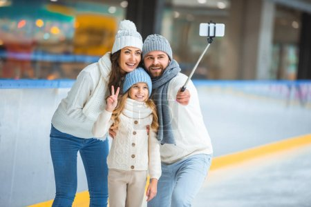 portrait of smiling family taking selfie on smartphone on skating rink
