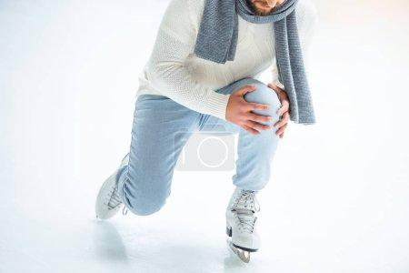 cropped shot of man injured knee while skated on ice rink