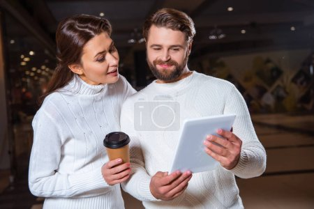 portrait of couple in white knitted sweaters using digital tablet together