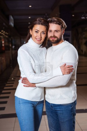 smiling couple in white sweaters hugging and looking at camera