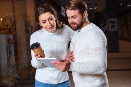 Photo for Couple in white knitted sweaters using digital tablet together - Royalty Free Image
