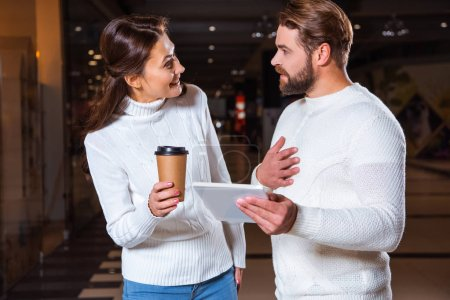 couple in white knitted sweaters looking at each other while using digital tablet together