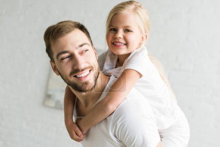 happy father and adorable little daughter hugging and having fun at home